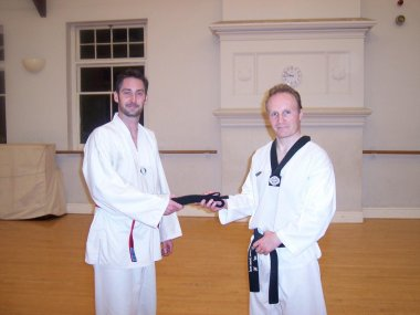 Mr Coombs receives his Black Belt from Master Evans